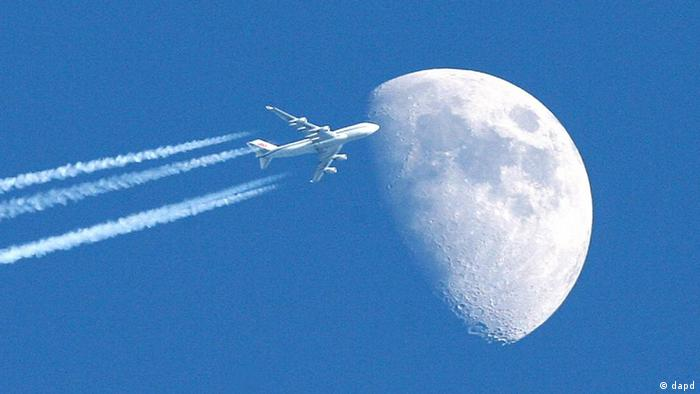 airplane flying against the moon