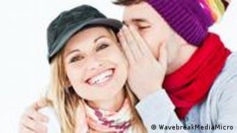 Ein Mann flüstert einer Frau etwas ins Ohr