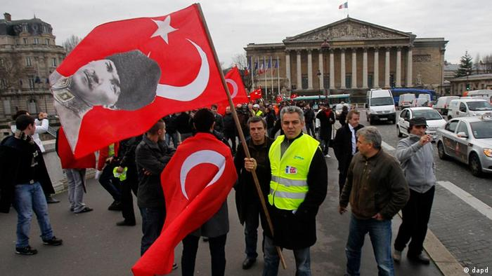 Demonstrators of France's Turkish community protest with Turkish flags outside the parliament in Paris, Thursday, Dec. 22, 2011. Lawmakers are to vote on a measure that would make it a crime in France to deny that the mass killings of Armenians in 1915 amounted to a genocide, a measure that could put France on a collision course with Turkey, a strategic ally. Turkey wants the killings left to historians and has lashed out at France, warning that it will withdraw its ambassador if the measure becomes law. On the Turkish flag is seen the picture of Mustafa Kemal Ataturk, founder of the new Turkey after WWW I.( AP Photo/Michel Euler)