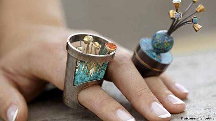 An einer weiblichen Hand sind zwei von Goldschmieden hergestellte, exzentrische Ringe zu sehen