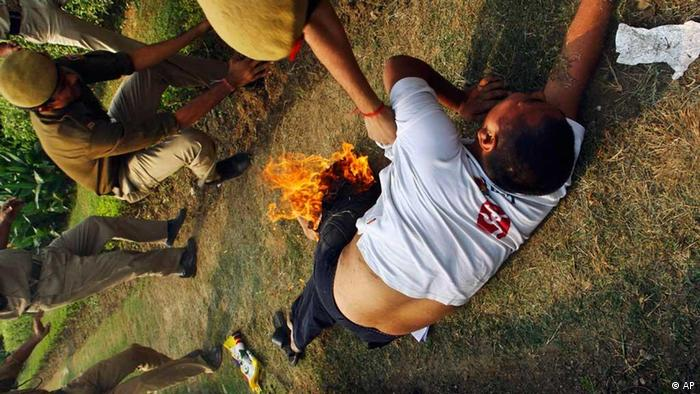 Indian police officers try to put out fire engulfing from the trousers of an exile Tibetan in New Delhi, India