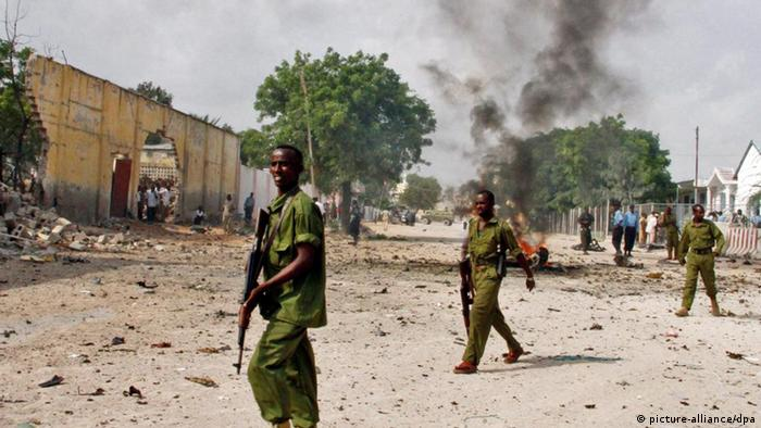 Somali security officers secure the scene of a suicide car bomb explosion