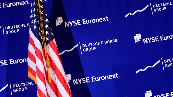 The logos of NYSE Euronext and Deutsche Borse are shown with an American flag prior to a news conference at the New York Stock Exchange, Tuesday, Feb. 15, 2011. The NYSE and Deutsche Boerse announced Tuesday that they plan to merge. (AP Photo/Mark Lennihan)