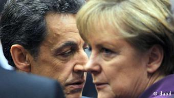 French President Nicolas Sarkozy, left, speaks with German Chancellor Angela Merkel during a round table session at an EU summit in Brussels on Friday, Dec. 9, 2011. The president of the European Council said Friday that a new intergovernmental treaty meant to save the euro currency will include the 17 eurozone states plus as many as six other European Union countries, but not all 27 EU members. (AP Photo/Geert Vanden Wijngaert)
