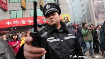 Files - A Chinese police officer disperses members of the public and media outside a McDonalds store after internet social networks called to join a 'Jasmine Revolution' protest in Wangfujing of central Beijing, China on 20 February 2011. Chinese police showed up in force to disperse a huge crowd of mostly onlookers gathered outside the fast food restaurant in Be