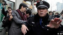 A man, 3rd from left, is detained by police officers in front of a cinema that was a planned protest site in Shanghai, China, Sunday, Feb. 20, 2011. Jittery Chinese authorities staged a show of force Sunday to squelch a mysterious online call for a Jasmine Revolution apparently modeled after pro-democracy demonstrations sweeping the Middle East. (AP Photo/Eugene Hoshiko)