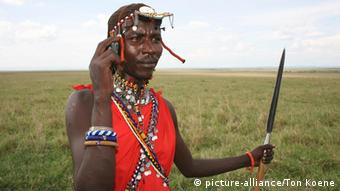 Maasai herdsman with a mobile phone and spear in an open field.
