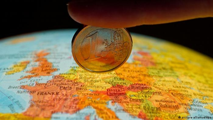 Finger holding one euro over globe