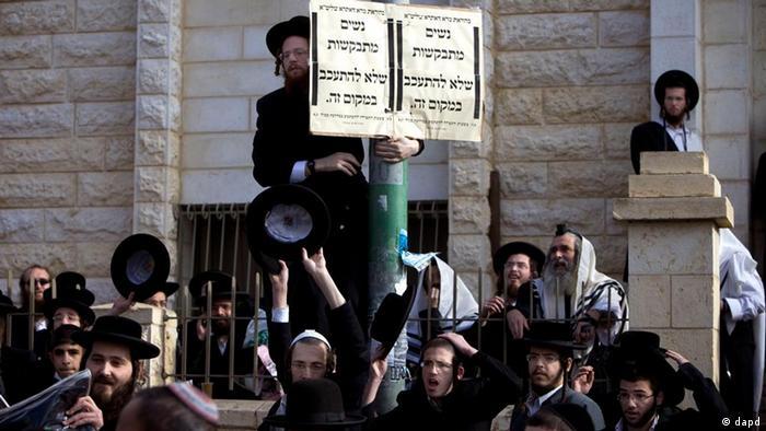 Ultra-orthodoxe Männer halten ein Plakat, auf dem sie Frauen auffordern, sich nicht vor einer Synagoge in beit Shemesh aufzuhalten (Foto: dapd)