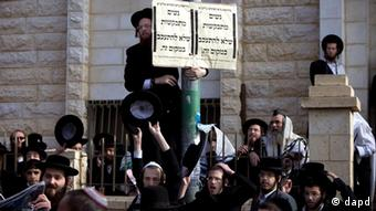 Ultra-Orthodox Jewish men gather around a sign that reads in Hebrew: Women are asked not to linger in this area outside a synagogue in the central Israeli town of Beit Shemesh, Monday, Dec. 26, 2011. The story of an 8-year-old American girl that has unwittingly found herself on the front line of Israel's latest religious war, drew new attention to the religious tensions in Beit Shemesh, a city of some 100,000 just outside Jerusalem, which has become a symbol of the growing violence of Jewish extremists in Israel in recent years. (Foto:Oded Balilty/AP/dapd)