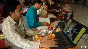 Indian men sit with open laptops