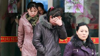 Mourners walk out from the door of a North Korean restaurant in Dandong
