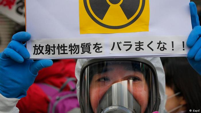 A protester in protective mask holds a placard during an anti nuclear rally in Tokyo, Sunday, March 27, 2011. Leaked water in Unit 2 of the Fukushima Dai-ichi plant measured 10 million times higher than usual radioactivity levels when the reactor is operating normally, Tokyo Electric Power Co. spokesman Takashi Kurita told reporters in Tokyo. The placard has a message that reads Don't spread radioactive substance. (Foto:Itsuo Inouye/AP/dapd)