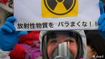 A protester in protective mask holds a placard during an anti-nuclear rally in Tokyo