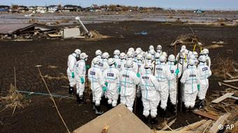 ADDS LOCATION PHOTO TAKEN - Japanese policemen gather as they prepare search for bodies in the area devastated by the March 11 earthquake and tsunami in Minamisoma, inside the 20-kilometer (12-mile) evacuation zone, in Fukushima Prefecture, northeastern Japan, Thursday, April 21, 2011. Japan declared the 20-kilometer (12-mile) area evacuated around its radiation-spewing nuclear power plant a no-go zone on Thursday, urging residents to abide by the order for their own safety or possibly face fines or detention. (AP Photo/Sergey Ponomarev)