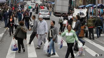In this July 7, 2011 photo, people shop in Sao Paulo, Brazil. The Central Bank expects that by the end of the year, 28 percent of Brazilians' disposable income will go toward servicing debts, compared to 16 percent in the still-recovering U.S. and single-digit figures in other developing nations. The bank also reports that 28 million Brazilians out of a population of 190 million are carrying more than $3,000 in debt, up 250 percent from six years ago. Some economists fear that these consumers have taken on too much debt and are being buried by Brazil's sky-high lending rates. They worry that if debt erodes their buying power, Brazil might face a recession. (AP Photo/Andre Penner)