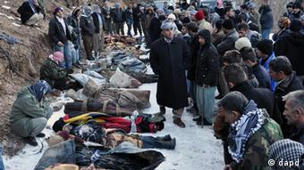 People look at bodies on the ground after Turkey's air force mistakenly killed 35 civilians in Uludere (Sirnak)
