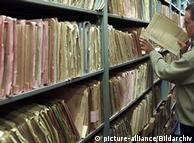 Mitarbeiter der Stasi-Unterlagenbehörde vor Aktenregal (Foto: picture-alliance/dpa)