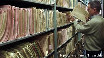 An employee puts away a file in rows in the archive