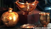 AUSSCHNITT: Die Nachbildungen von Goldgefäßen aus dem Schatz des Priamos werden am Donnerstag auf einer Pressekonferenz von einem Fotografen im Berliner Schloß Charlottenburg abgelichtet. Die Originale, die ca. 2300 v.Chr. angefertigt wurden, befinden sich im Puschkin-Museum in Moskau. Wenige Tage vor der Troja-Ausstellung in der russischen Hauptstadt wird am 12.4.96 in der Spreemetropole eine Schliemann-Ausstellung eröffnet. (COLORplus)