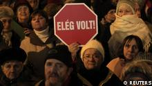 A woman holds up a sign during a protest in central Budapest January 2, 2012. The demonstrators are protesting against the government and new Basic Law which replaced the country's Constitution on January 1, in a show of angst at what they say is the ruling Fidesz party's heavy-handed policies. The sign reads Enough! REUTERS/Laszlo Balogh (HUNGARY - Tags: POLITICS CIVIL UNREST)