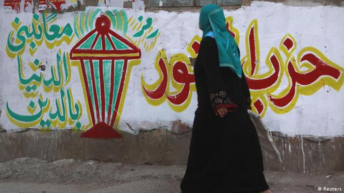 A woman walks past an Al Nour graffiti reading Together hand in hand we build the country through religion