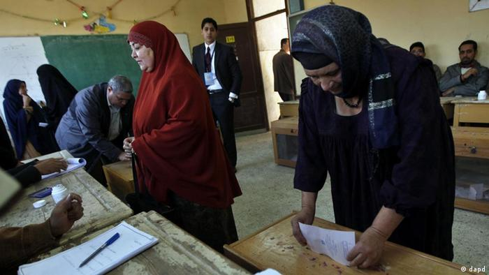 An Egyptian woman casts her vote as another checks for her name at a polling center during the third round of the elections for Egypt's parliament, in Qalyobeia, Egypt Tuesday, Jan. 3, 2012. Egyptians lined up in front of polling centers in nine provinces to cast their ballots Tuesday in the third round of the country's first parliamentary elections following the ouster of Hosni Mubarak.(Foto:Khalil Hamra/AP/dapd)