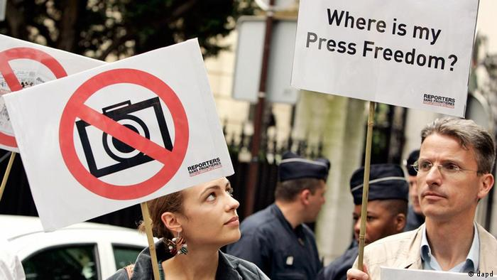 Members of French media watchdog Reporters Without Borders gather near the Iranian embassy in Paris, during a demonstration for press freedom in Iran, Thursday June 18, 2009 in Paris. Two riot policemen are seen standing guard rear center. (ddp images/AP Photo/Francois Mori)