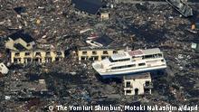 Redaktionshinweis: Verwendung des Bildes nur zur redaktionellen Berichterstattung und bei Nennung The Yomiuri Shimbun, Motoki Nakashima! Keine Werbung! JAPAN OUT, CREDIT MANDATORY +++ ARCHIV: Eine Faehre liegt zwei Tage nach dem Erdbeben und dem Tsunami in Otsuchi in der Praefektur Iwate in Japan auf einem Haus. Um 14.46 Uhr an einem ganz normalen Freitagnachmittag standen die Uhren in Japan ploetzlich still. Ein verheerendes Erdbeben der Staerke 9.0 erschuetterte den Nordosten des Landes und loeste einen riesigen Tsunami aus. Teile der Kueste wurden dem Erdboden gleichgemacht und im Atomkraftwerk Fukushima-Daiichi bahnte sich die groesste Atomkatastrophe seit Tschernobyl an. Insgesamt kamen bei den Naturkatastrophen am 11. Maerz fast 16.000 Menschen ums Leben, mehr als 3.000 gelten nach wie vor als vermisst. Foto: Yomiuri Shimbun/Motoki Nakashima/AP/dapd