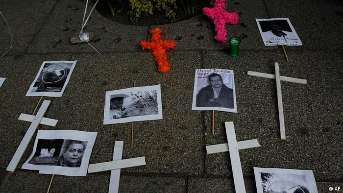Crosses and pictures of people killed or abducted by alleged drug gangs are placed on a sidewalk during a protest to demand peace and justice in Mexico City, Sunday, Dec. 11, 2011. (AP Photo/Marco Ugarte)
