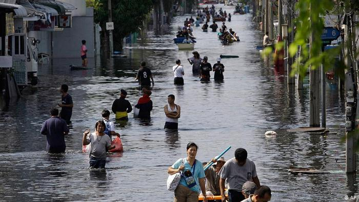Thai residents carry their belongings along floods as they move to higher ground at Bangkok's Don Muang district, Thailand on Monday Oct. 31, 2011. Thailand's prime minister said Monday that she hopes the process of draining floodwater through Bangkok can be sped up now that peak high tides that saw the city's main waterway rise to record levels have passed. (ddp images/AP Photo/Aaron Favila)