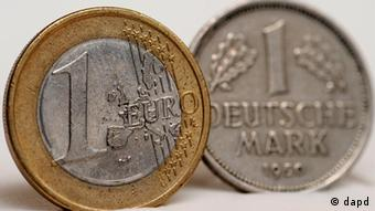One euro coin next to one deutschmark coin