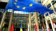 Die Fahnen der EU-Mitgliedsstaaten schmücken den Eingang des EU-Ratsgebäudes in Brüssel (Archivfoto vom 16.06.2004). Größer ist die Europäische Union geworden, besonders in Brüssel. Der ovale Sitzungssaal der EU-Kommission, in dem die Kommisssare aus den seit einem Jahr 25 Mitgliedstaaten beraten, sieht wie ein gigantisches Raumschiff aus. Im Gebäude des Ministerrates ist der Konferenztisch jetzt so riesig, dass der jeweilige Sprecher nur dank eines eingebauten Bildschirms auch am anderen Ende des Raumes noch erkennbar ist. EPA / Olivier Hoslet (zu dpa-THEMENPAKET - Stichtag: 1. Mai Die erweiterte EU: Ankunft im politischen Alltag) +++(c) dpa - Bildfunk+++