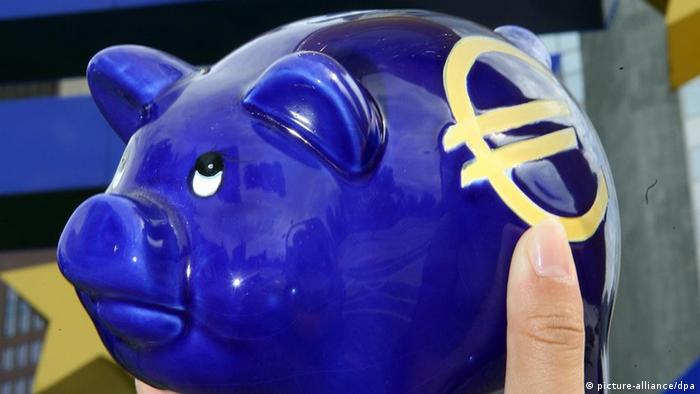 ARCHIV - Illustration - Ein überdimensionaler Euro wird am 15.08.2007 vor der Europäischen Zentralbank (EZB) in Frankfurt an ein Sparschwein gehalten. Das neue Hilfspaket für Griechenland wird einen Umfang von 109 Milliarden Euro haben. Das geht aus der Abschlusserklärung des Euro-Krisengipfels vom Donnerstag (21.07.2011) in Brüssel hervor. Der Beitrag der Banken wird mit 37 Milliarden Euro angegeben. Foto: Boris Roessler dpa +++(c) dpa - Bildfunk+++
