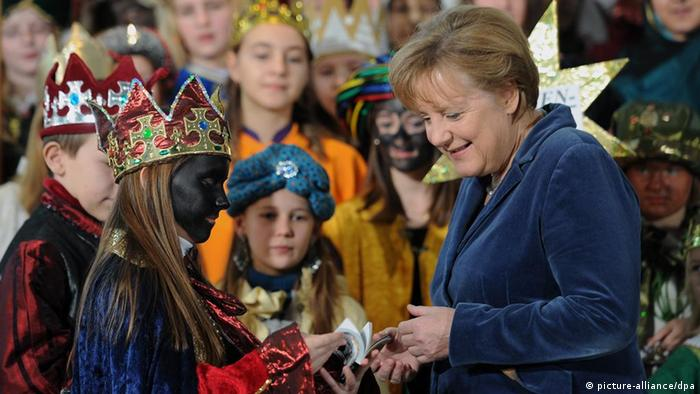 Chancellor Angela Merkel greets Sternsinger at the German Chancellery in 2012