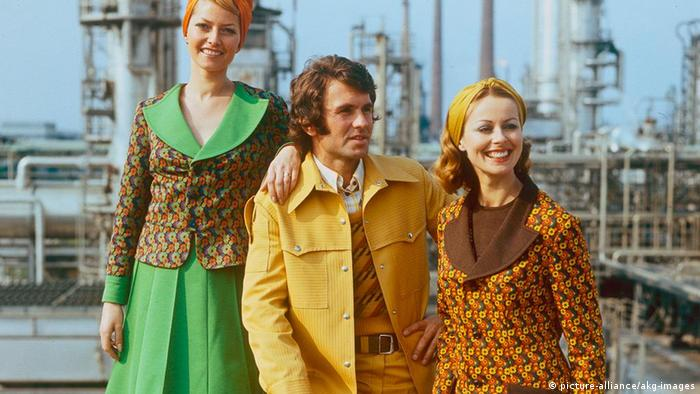 A man and two women modelling clothes in an oil refinery