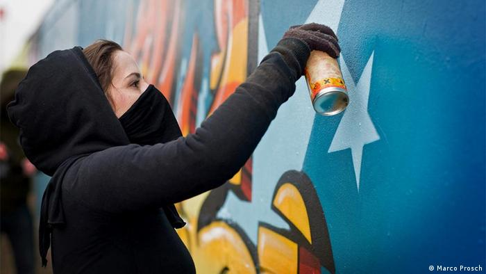 A graffiti artist at work with a spray can