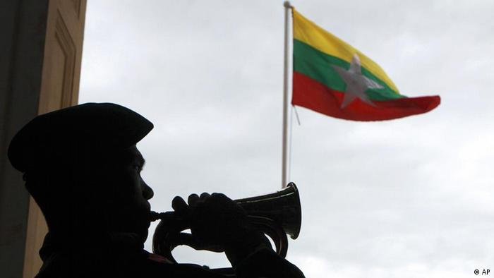 A member of the Guard of Honor toots as a new State Flag of Myanmar is hoisted outside the town hall Thursday, Oct. 21, 2010, in Yangon, Myanmar. Military-ruled Myanmar has unveiled the new national flag - with three horizontal stripes of yellow, green and red with a big white star in the middle - Thursday, just two weeks before an election that the government calls a major step in a transition to democracy but critics say is a sham (photo: AP/Khin Maung Win).