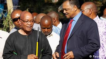 South Africa's President Jacob Zuma (L) holds a spear, as U.S. civil rights activist Reverend Jesse Jackson (R) looks on, after an ox was sacrificed as part of a cleansing ceremony ahead of the upcoming African National Congress (ANC) centenary celebration in Bloemfontein January 7, 2012. South Africa's ruling ANC celebrates its 100th birthday on Sunday. The long-banned liberation movement took power in 1994 after Mandela negotiated an end to apartheid with the white-minority government. Capitalising on its role as the standard bearer in the fight against apartheid, the party has dominated politics since then, but bitter faction-fighting and accusations of rampant corruption have raised questions about how long it will continue to lead Africa's biggest economy. REUTERS/Siphiwe Sibeko (SOUTH AFRICA - Tags: POLITICS ANNIVERSARY RELIGION)