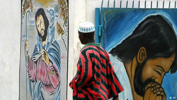 A Muslim man walks past a mural of Jesus Christ