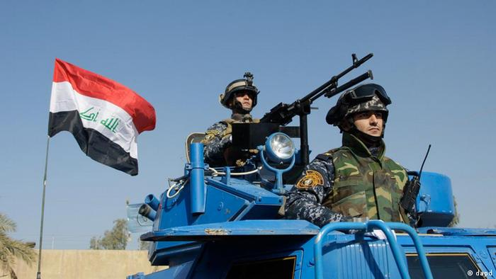 The Iraqi flag waves during a federal Police parade in Baghdad, Iraq