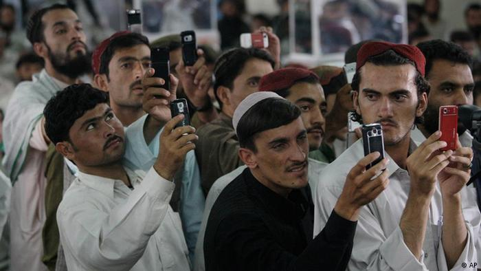 Afghan men use mobile phone cameras to take pictures of presidential candidate and former Finance Minister Ashraf Ghani Ahmadzai during an election campaign stop in Kandahar, Afghanistan Saturday Aug. 15, 2009. Afghans will head to the polls on Aug. 20 to elect the new president.(AP Photo/David Guttenfelder)