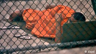 A Guantanamo detainee glances up while resting on a foam pad