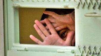 a Guantanamo detainee peers through his hands from inside his cell at the Camp Echo detention facility at the U.S. Naval Base, in Guantanamo Bay, Cuba.