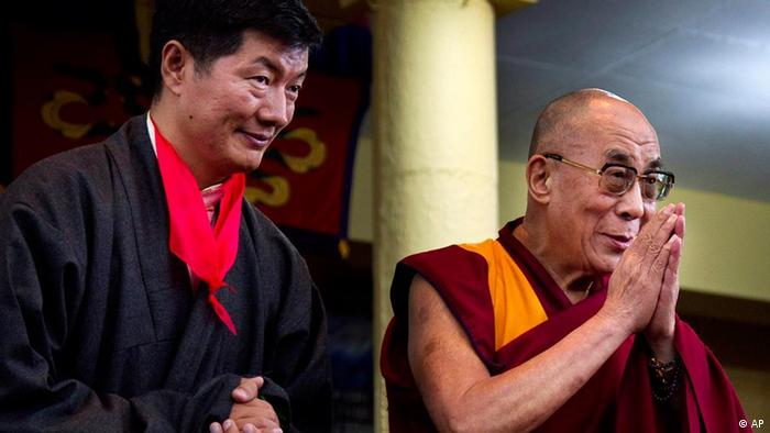Lobsang Sangay, left, the new prime minister of Tibet's government in exile, stands next to Tibetan spiritual leader the Dalai Lama as he greets the crowd at his swearing-in ceremony (Photo:Ashwini Bhatia/AP/dapd)