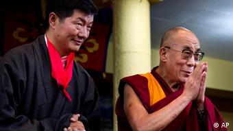 Lobsang Sangay, left, the new prime minister of Tibet's government in exile, stands next to Tibetan spiritual leader the Dalai Lama as he greets the crowd at his swearing-in ceremony at the Tsuglakhang Temple in Dharmsala, India, Monday, Aug. 8, 2011. The Harvard-trained legal scholar has been sworn in as head of the Tibetan government in exile and is replacing the Dalai Lama as political leader of the exile movement.