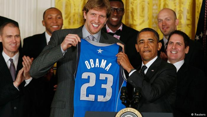 U.S. President Obama (2nd R) receives a team jersey from Dirk Nowitzki (3rd L) while hosting the 2011 NBA champions Dallas Mavericks in the East Room at the White House in Washington, January 9, 2012. At right is owner Mark Cuban. REUTERS/Larry Downing