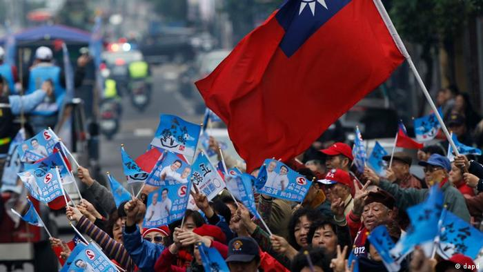 Supporters of Taiwan's President and presidential candidate Ma Ying-jeou wave flags during an election rally