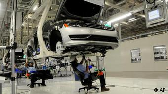 Workers inspect undercarriage (AP Photo/Billy Weeks)