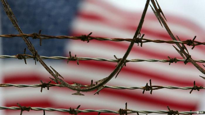 A flag waves behind the barbed and razor-wire at the detention compound on Guantanamo Bay